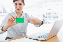 Young businesswoman pointing to green business card Royalty Free Stock Images