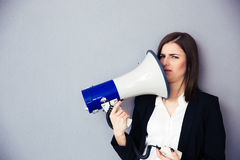 Young businesswoman points megaphone at herself Royalty Free Stock Images