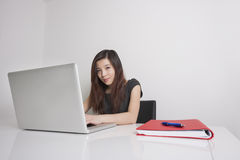 Young businesswoman. Portrait of confident young businesswoman using laptop in office royalty free stock photography