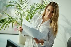 Young businesswoman poses with documents in hand Stock Image
