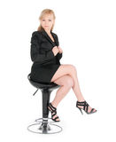 Young businesswoman posing on a bar chair over white background.  Royalty Free Stock Photography