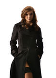 A young businesswoman posing in a long black coat Stock Images