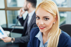Young businesswoman posing with a smile in office with Stock Photo