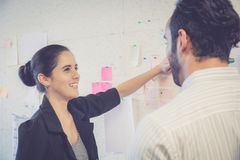 Young businesswoman with present profit and secretary while giving presentation in office. Royalty Free Stock Image