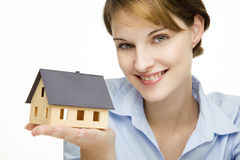 Young businesswoman presenting a model house. Young friendly smiling businesswoman presenting a model house Stock Photography