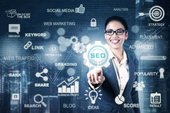 Young businesswoman presses SEO icon. Picture of a young businesswoman pressing a virtual SEO icon on the digital screen. SEO concept Royalty Free Stock Photo