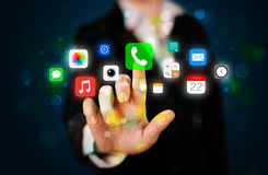 Young businesswoman pressing colorful mobile app icons with boke Royalty Free Stock Photo