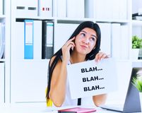 Young businesswoman in the process of useless conversation with the client or boss. Effective communication concept. Effective communication concept. Young stock photography