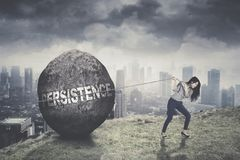 Young businesswoman pulling persistence word. On a stone while climbing on the mountain with cloudy sky background Royalty Free Stock Images