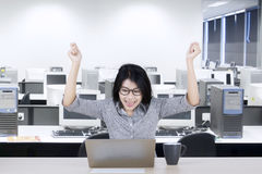 Young businesswoman raising hands on office Royalty Free Stock Image