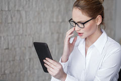 Young businesswoman reading bad news on tablet Royalty Free Stock Image