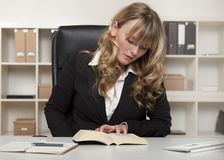Young businesswoman reading a book at work Royalty Free Stock Photo