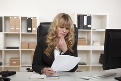 Young businesswoman reading through a document Stock Images