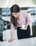 Young businesswoman reading document while holding coffee in office Stock Images