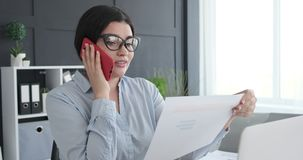 Businesswoman reading document while talking on mobile phone. Young businesswoman reading a document while talking on mobile phone at office stock footage