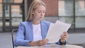 Young businesswoman reading documents while sitting outdoor. 4k high quality, 4k high quality stock footage