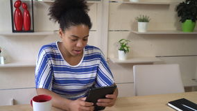 Young businesswoman reading documents on the touch screen tablet. Mixed race attractive woman using app. Female siting at the office sent email via internet on stock footage