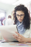 Young businesswoman reading notepad at creative office with colleagues in background Stock Images