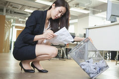 Young businesswoman reading piece of paper from the trash can in office Stock Photography