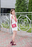 Young girl in a white dress with a red handbag walking around the city royalty free stock photos