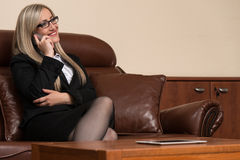 Young Businesswoman Relaxes Sitting In The Office Stock Photo