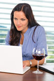 Young businesswoman relaxing home wine surfing internet Stock Images