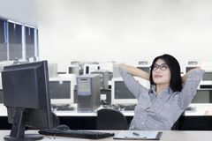 Young businesswoman relaxing in the office. Picture of young businesswoman relaxing on the chair while daydreaming in the office Royalty Free Stock Photo