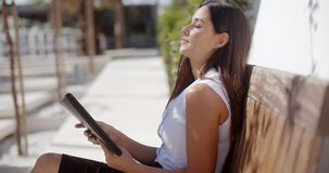 Young businesswoman relaxing on an outdoor bench stock video footage