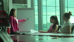 Young businesswoman reports information to colleagues in office. The general manager presents some information in office center. Two young women listening the stock footage