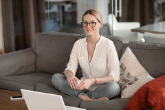 Young businesswoman resting. Young business woman relaxing, sitting on the couch, looking out the frame, drinks coffee Stock Photography