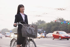 Young businesswoman riding a bicycle on the street, Beijing Royalty Free Stock Photography