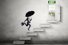 Young businesswoman runs toward the exit door Stock Photo