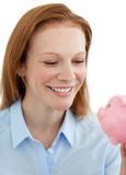 Young businesswoman saving money in a piggy-bank Stock Images