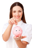 Young businesswoman saving money in a piggybank. Young brunette businesswoman saving money in a piggybank against a white background Stock Images