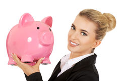 Young businesswoman saving money in piggybank.  Royalty Free Stock Photo