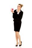 Young businesswoman saving money in piggybank Royalty Free Stock Photos