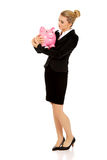 Young businesswoman saving money in piggybank.  Royalty Free Stock Images