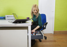 Young businesswoman searching something in drawer with laptop and file folder on desk Royalty Free Stock Image