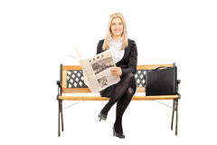 Young businesswoman seated on a bench holding newspaper Royalty Free Stock Photo