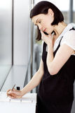 Young businesswoman or secretary making an appointment in a diary Royalty Free Stock Photography
