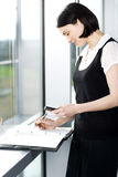 Young businesswoman or secretary making an appointment in a diary Stock Photo
