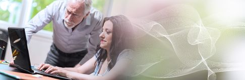 Young businesswoman and senior businessman working together; panoramic banner royalty free stock photo