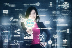 Young businesswoman and SEO icon. Picture of a young female entrepreneur pressing a SEO icon on the virtual screen. Concept of Search Engine Optimization Royalty Free Stock Photos