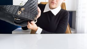 Young businesswoman shaking out her leather handbag on office desk stock photography