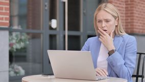 Young businesswoman in shock while working on laptop outdoor stock video footage