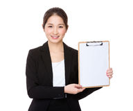 Young Businesswoman showing a blank page of clipboard. Isolated on white background Stock Photos