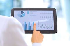 The young businesswoman showing graphs by finger at the digital tablet stock images
