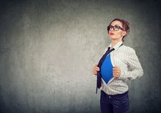 Business woman showing a super hero suit underneath her shirt. Young Businesswoman showing a super hero suit underneath her shirt royalty free stock photography