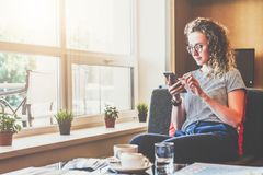 Young businesswoman sits on sofa near window,uses smartphone. Girl chatting, blogging, checking email, working. Student studying. Online marketing,education,e Royalty Free Stock Photography