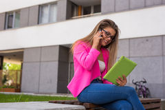 Young businesswoman sitting on a bench with tablet and smartphon Royalty Free Stock Image